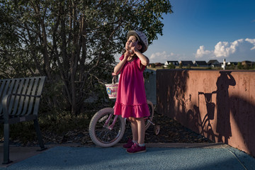 Girl removing bicycle helmet while standing at park