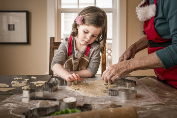 Granddaughter helping grandmother in making Christmas cookies on table