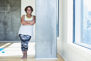 Happy woman with arms crossed looking away while leaning on architectural column in yoga studio