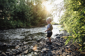 Side view of boy throwing pebbles in river