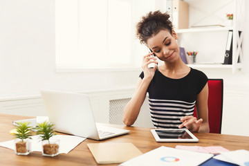 Happy business woman at work talking on phone