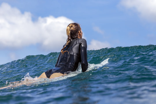 Rear view of woman wearing wetsuit while surfing on sea against cloudy sky