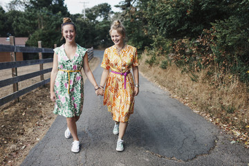 Cheerful female friends holding hands while walking on country road