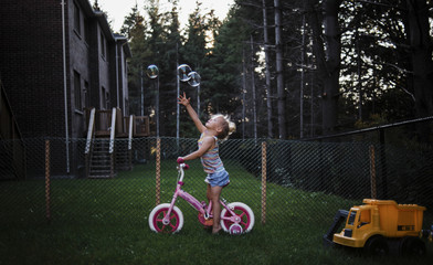 Playful girl reaching for bubbles while sitting on bicycle against fence at yard