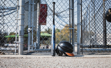 Baseball bat and sports helmet against chainlink fence at playing field during sunny day