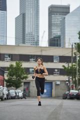 Sporty woman jogging on street in city
