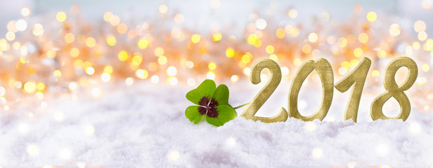 Silvester, New Year 2018  -  Snow landscape with golden bokeh background and four-leafed clover