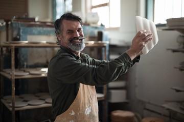 Portrait of male potter checking ceramic bowl