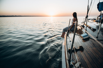 Photo on which a beautiful girl with long hair sits on a yacht and admires the beautiful sunset