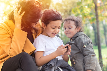 Happy family using mobile phone in the park.