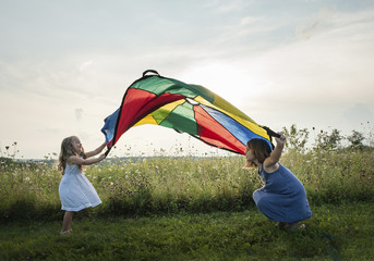 Playful sisters playing with colorful textile on grassy field against sky