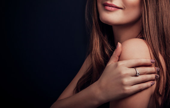 Beautiful woman with long hair and manicure wearing a ring