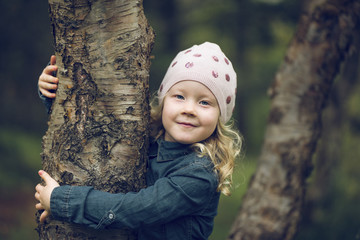Portrait of cute girl embracing tree trunk at park