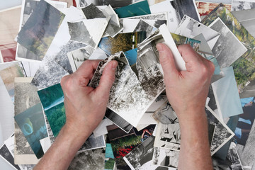 The old man is tearing the old photographs into small pieces to forget the past lived life.