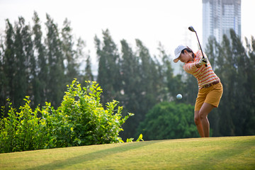 Asian woman golf player hitting chips golf ball to the hole on the green with golf club in the sunny day, copy space.  Lifestyle Concept.