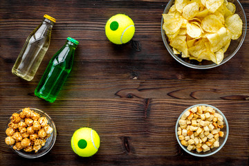 Snacks for watching sport matches and games on TV. Crisps, popcorn, rusks near drink and ball on dark wooden background top view copyspace