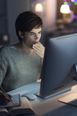 Woman working at night and yawning