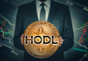 businessman holding big shiny bitcoin in hands in front of stock market data chart background and hodl word on bitcoin