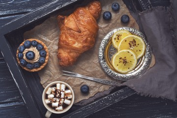 Croissant and cake with blueberries on a wooden tray. Lemon and vintage fork for lemon. Photo with toning.