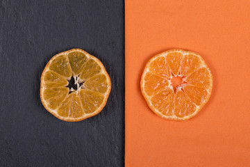Slices of mandarin lies on orange napkin and on black slate. Concept of healthy, organic, vegan food, vitamins. Top view. Fresh orange, tangerine background