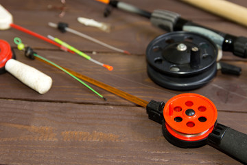 Tackle for winter fishing. Fishing rods and accessories on a wooden table. The view from the top.