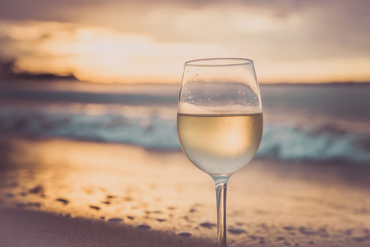 A glass  of white wine on the beach at sunset. Travel vacations concept.