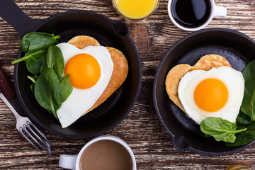 Valentine's day breakfast or brunch with  heart shape fried egg in cast iron skillet