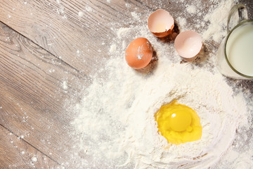 The top view of the egg, beaten into flour, a glass of fresh milk, cooking the dough on the background of a wooden table. Flat lay, copy space.