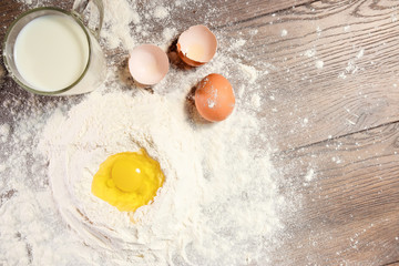 The top view of the egg, beaten into flour, a glass of fresh milk, cooking the dough on the background of a wooden table.