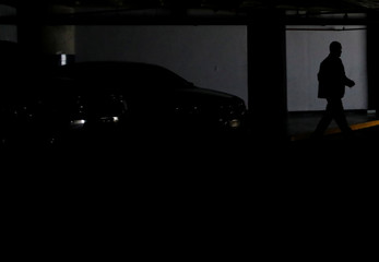 A man walks at a parking garage, during a massive blackout in Caracas