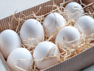 Fresh chicken eggs are in a box with wooden shavings