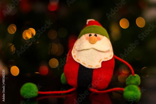 papa noel de fieltro con luces navideñas de fondo\