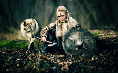 Viking Warrior Woman  with a woolf in the woods. Reconstruction of a medieval scene