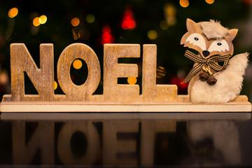 Palabra Noel reflejada con zorro y bokeh navideño
