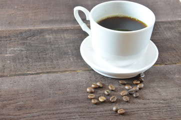 Coffee cup and beans on wooden table background with copy space