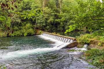 small dam with spillways on the river Eume with shores covered with vegetation in a typical Atlantic oak forest in Galicia