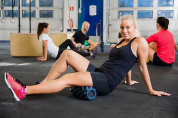 Fit Woman Exercising With Foam Roller In Health Club