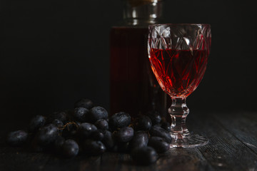 Red wine and grapes placed on table against black background