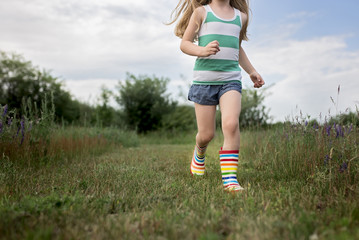 Low section of girl running on field