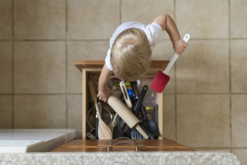Overhead view of baby boy removing kitchen utensils from drawer