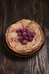 pancakes with frozen berries pile in a brown plate on a dark wooden table on a dark gray background