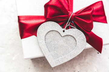 Gift tied with ribbon and red heart on vintage background. Valentine's day...