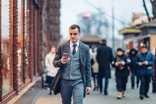 Young man using the phone while walking along the street