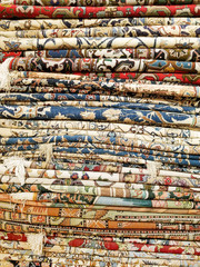 Vertical stack of colorful Middle Eastern style rugs and carpets fabric background pattern texture