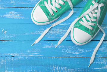green textile sneakers on a blue wooden background