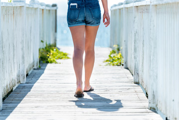 Woman walking to the beach on boardwalk