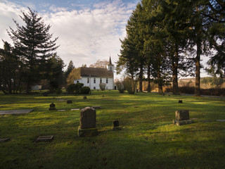 Historic Rural Church and Graveyard. A vintage white church built in the early 20th century sits waterside next to a cemetery on an island in the Pacific Northwest.