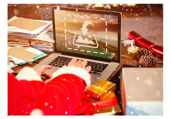 Santa Using Laptop Surrounded by Letters