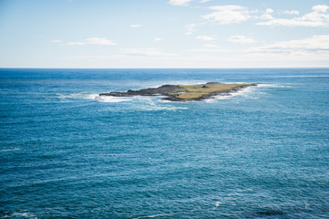 A small island of the coast of Iceland on a bright blue bird day.