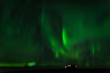 Green northern lights in Iceland with a camper van on the ground.